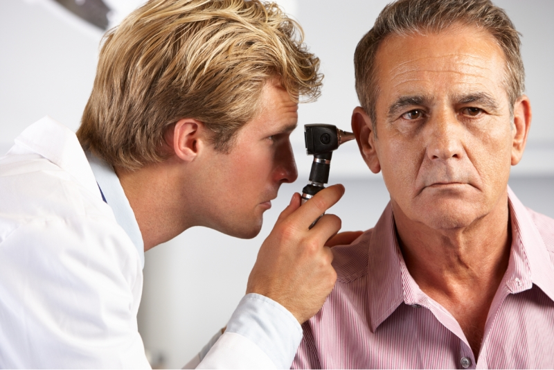 An audiologist examining a patient's ear