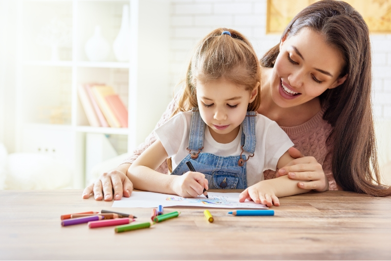 A mom and her daughter who is coloring after being treated for tonsilitis